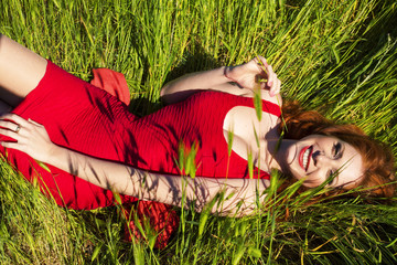 happy smiling woman with red hair lying on field of grass