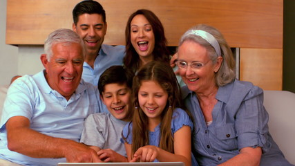 Extended family using laptop together on couch