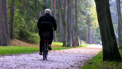 Senior woman riding a bike in the park