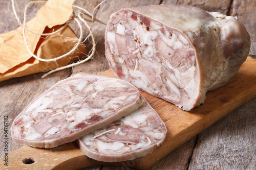 Cut headcheese on chopping board close-up - 64767182