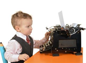 kleiner junge mit großer alter schreibmaschine