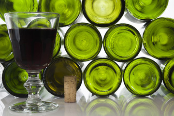 Rotweinglas mit Korken vor Weinflaschen vor weißem  Hintergrund