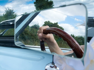Reflection of a human's hand in the mirror of a car