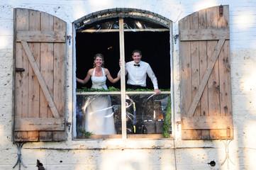 Brautpaar schaut aus einem Tor