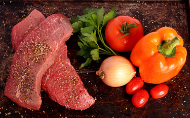 Two raw steaks with vegetables and spices on brown background