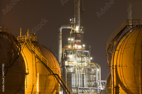 A large oil-refinery plant with gas storage tanks - 64771780