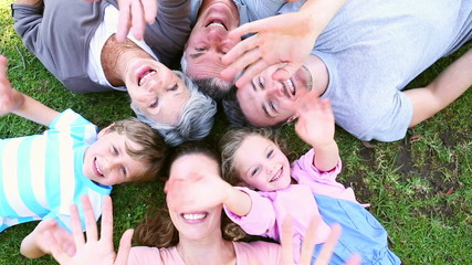 Extended family lying in the park together smiling up at camera