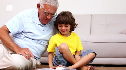 Senior man sitting on floor with his grandson looking at photo a