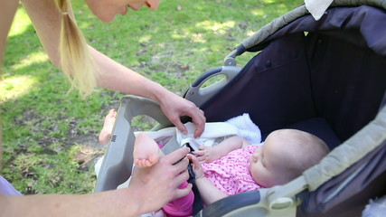 Mother tending to her baby girl in her pram in the park