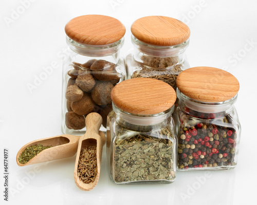 Fotobehang Kruiden jars and wooden spoons with spices isolated on white
