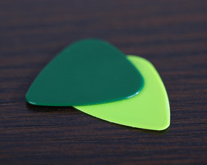 Colorful plectrums on wooden background