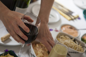 Glass of red wine in womans hand at buffet.
