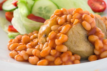 Detail of a jacket potato with baked beans and a salad.