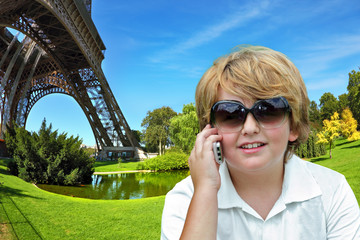 Beautiful blond boy chatting on a cell phone
