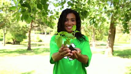 Happy environmental activist holding a shrub
