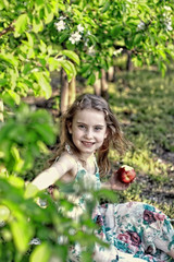 girl in apple orchard eating an apple