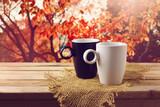 Biała i czarna filiżnka na drewninym stole - 64780172