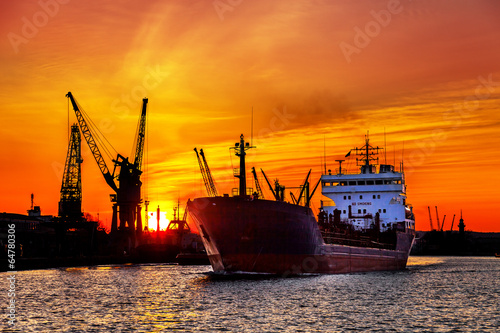 Silhouette of sea port cranes over sunset - 64780306