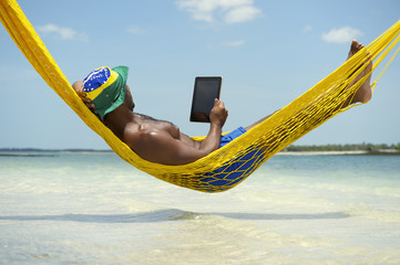 Brazilian Man Relaxing with Tablet in Beach Hammock