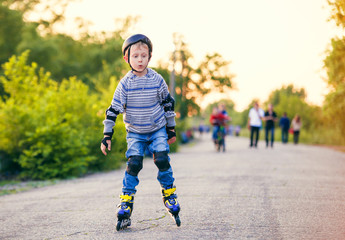 Little roller skater in the evening park