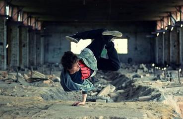 Teenager dancing break dance in the old brickworks