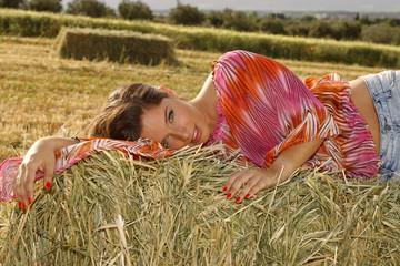 Mujer acostada en la hierba en un atardecer de verano