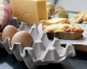 Eggs in the tray and slices of hard cheese for hot sandwiches