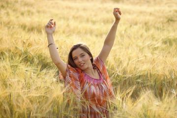 Mujer guapa lllena de felicidad en un campo de trigo
