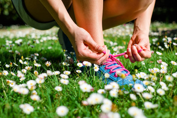 Female runner lacing running shoes in spring