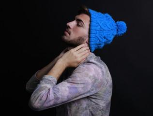 Joven guapo posando con gorro azul