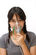 a cute asian  girl with a mask for inhaler