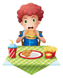 A curly-haired boy eating at a fastfood restaurant