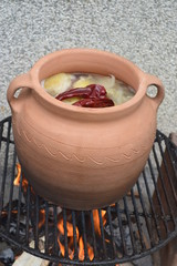 Clay pot with cabbage on fire