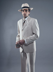 Mafia fashion man wearing white striped suit and hat. Holding vi