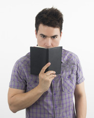 Man Think and hides his face behind a book.