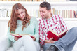 Cheerful young man and woman reading different books together wh