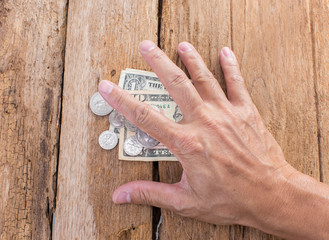 Hand with dollar on wooden background