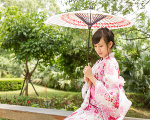 Asian woman wearing a yukata with an umbrella in Japanese style