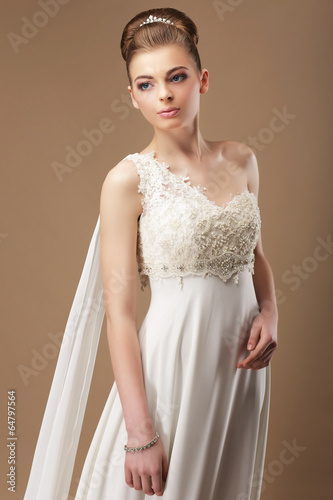 Femininity. Gentle Woman in Lacy Dress over Beige Background