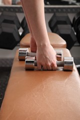 Frau im Fitnessstudio greift nach Hanteln