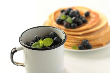 Cup with blueberries fruits and mint leafs and stack of pancakes