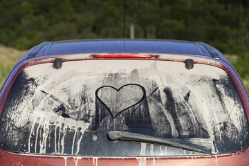 Dirty rear window of the car and inscription of a heart