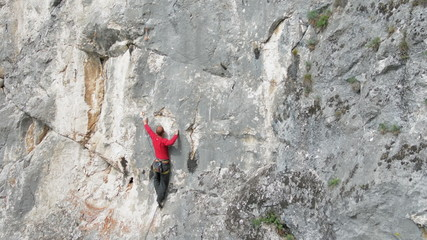 Rock climber tries dificult move and falls