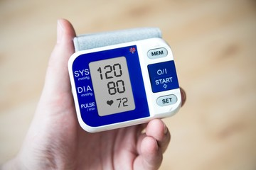 Hand holding blood pressure gauge