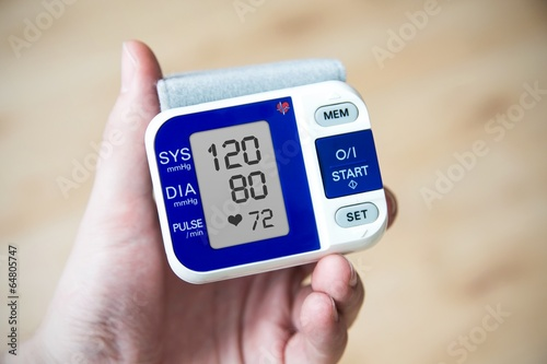 canvas print picture Hand holding blood pressure gauge