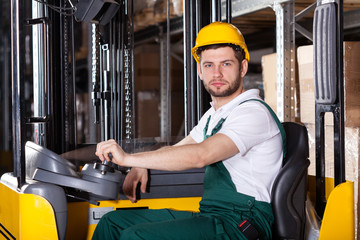 Storehouse employee driving on forklift
