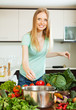 Long-haired woman cooking from  vegetables in  kitchen