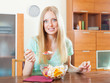Positive  blonde woman eating  fruit salad
