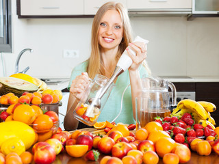 Happy girl making fruits cocktail with  electric blender