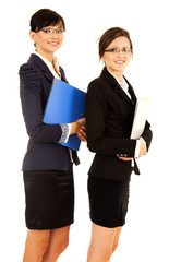 two happy young business women standing and smiling